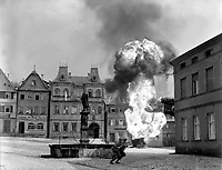 Two anti-tank Infantrymen of the 101st Infantry Regiment, dash past a blazing German gasoline trailer in square of Kronach, Germany.  April 14, 1945.  T4c.  W.J. Rothenberger.  (Army)<br /> NARA FILE #:  111-SC-206235<br /> WAR &amp; CONFLICT BOOK #:  1091