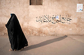KIRKUK, IRAQ:  An Iraqi woman walks past a mosque in Kirkuk...Security is tightened in the volatile Iraqi city of Kirkuk the day before the national elections.  Kirkuk is home to Kurds, Arabs, and Turkmen and has been so violently divided that the city could not participate in the 2005 elections.