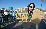 A man holding signs was one of hundreds of participants in a February 14 2015 march in Pasco, Washington, that demanded justice for the killing of Antonio Zambrano Montes by three Pasco police officers on February 10.