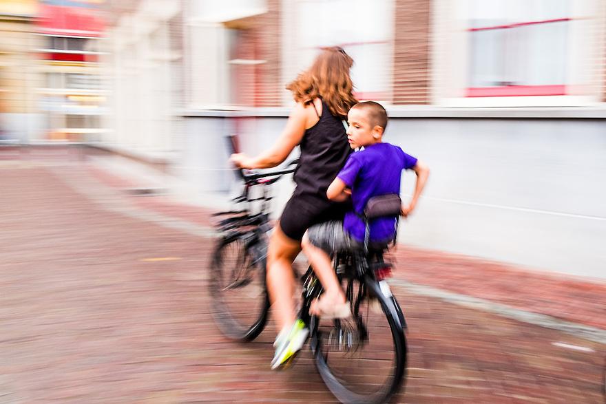 Nederland, Utrecht, 20 juli 2014<br /> Moeder op de fiets met kind achterop.  <br /> Foto (c) Michiel Wijnbergh