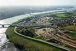 Nederland, Gelderland, Nijmegen, 24-10-2013; rivier de Waal met (de toerit naar) de Waalbrug, gezien vanuit het Oosten, daarachter de spoorbrug met fietspad (De Snelbinder) en tenslotte de nieuwe stadsbrug van Nijmegen De Oversteek. Rechts van de rivier grondwerkzaamheden voor de dijkteruglegging Lent (Ruimte voor de Rivier). De dijken worden landinwaarts verplaats en er wordt een nevengeul gegraven. De huizen op de dijk blijven bestaan en komen te liggen op het Stadseiland Veur-Lent Nijmegen. In de verte de rookpluimen van de energiecentrale Electrabel Nederland.<br /> First bridge the Waal bridge on the river Waal, next the railway bridge with cycle path De Snelbinder (The Luggage strap) and finally the new city bridge of Nijmegen De Oversteek (The Crossing). Right of the river groundwork for the Dike relocation of Lent (project Ruimte voor de Rivier: Room for the River). <br /> luchtfoto (toeslag op standaard tarieven);<br /> aerial photo (additional fee required);<br /> copyright foto/photo Siebe Swart.