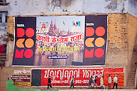 Indian people walking past TATA Docomo posters by the Ganges in holy city of Varanasi, Benares, Northern India