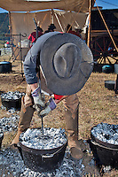 In October, the 22nd Annual Lincoln County Cowboy Symposium brought together  chuckwagon crews and cooks from ranches all over the southwest to compete in preparing food for a hungry crowd. David Griffith of the Rockin Dubya checks the buiscuits in his  dutch oven.s