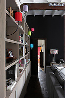 In the living room one wall has been painted a deep black to match the brick floor and the adjacent wall is lined with a long bookcase
