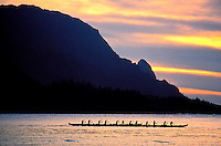 Outrigger canoes in Hanalei Bay at dusk, with the Na Pali Coast in the background