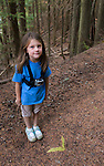 A six year old girl stands along a trail in Bonner County, Idaho wearing a GoPro chesty harness and GoPro Hero2 camera.