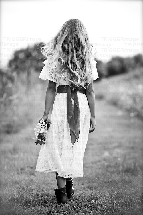 Female youth outdoors holding flowers walking away from camera