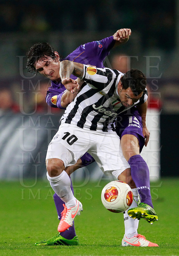 Calcio, ritorno degli ottavi di finale di Europa League: Fiorentina vs Juventus. Firenze, stadio Artemio Franchi, 20 marzo 2014. <br /> Juventus forward Carlos Tevez, of Argentina, foreground, is challenged by Fiorentina defender Stefan Savic, of Montenegro, during the Europa League round of 16 second leg football match between Fiorentina and Juventus at Florence's Artemio Franchi stadium, 20 March 2014. Juventus won 1-0 to advance to the round of eight.<br /> UPDATE IMAGES PRESS/Isabella Bonotto