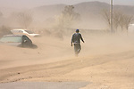 A man braves the strong winds at the 1000 block of Blodgett Street in San Jacinto on Monday, October 22, 2007. Many of the vehicles on this street were buried under the sand.