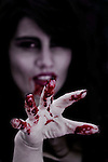 Blurred portrait of a woman with her right hand with blood dripping focused and reaching to the camera.