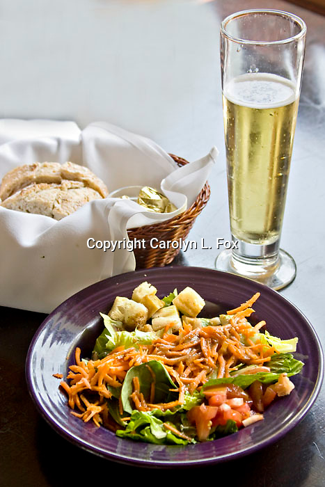 A beer is served with a salad and bread.