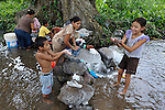 Women wash their laundry in a stream while their children blow bubbles on the La Lempira Cooperative, near Ceibita, Honduras. La Lempira is an agricultural project which has been seized by armed peasants who claim the land is rightfully theirs under the country's agrarian reform law.