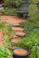 Recycled garden with old car tires and car seat bench, wide view