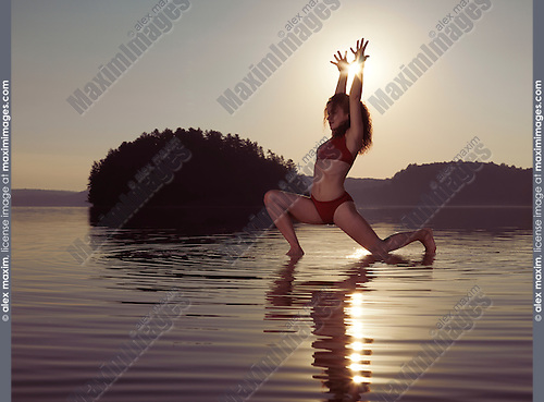 Young woman practicing Hatha yoga artistic variation of Low Lunge pose on a floating platform in water on the lake during misty sunrise in the morning. Yoga Anjaneyasana posture. Muskoka, Ontario, Canada.