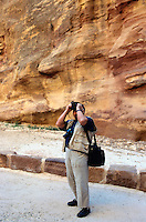 "Jordan. Petra.The archeological site is part of the UNESCO world heritage project.  The Nabataeans were an arabian industrious tribe which settled down in southern Jordan 2000 years ago. Petra is located at the bottom of a spectacular deep gorge surrounded by mountains. German tourist takes pictures while walking down the ""Siq"", a narrow and long path through a fault due to a prehistoric earthquake.  © 2002 Didier Ruef"