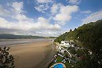 "Portmeirion, in North Wales, is a resort, where no one has ever lived. A self-taught Welsh architect named Sir Clough Williams-Ellis built it out of architectural salvage between the 1920s and 1970s, loosely based on his memories of trips to Portofino. Including a pagoda-shaped Chinoiserie gazebo, some Gothic obelisks, eucalyptus groves, a crenellated castle, a Mediterranean bell tower, a Jacobean town hall, and an Art Deco cylindrical watchtower. He kept improving Portmeirion until his death in 1978, age 94. It faces an estuary where at low tide one can walk across the sands and look out to sea. At high tide, the sea is lapping onto the shores. Every building in the village is either a shop, restaurant, hotel or self-catering accomodation. The village is booked out at high season, with numerous wedding receptions at the weekends. Very popular amongst the English and Welsh holidaymakers. Many who return to the same abode season after season. Hundreds of tourists visit every day, walking around the ornamental gardens, cobblestone paths, and shopping, eating ice-creams, or walking along the woodland and coastal paths, amongst a colourful assortment of hydrangea, rhododendrons, tree ferns and redwoods. The resort boasts two high class hotels, a la carte menus, a swimming pool, a lifesize concrete boat, topiary, pools and wishing wells. The creator describes the resort as ""a home for fallen buildings,"" and its ragged skyline and playful narrow passageways which were meant to provide ""more fun for more people."" It does just that.///Portmeirion Hotel overlooking the estuary Afon Dwyryd towards Porthmadog and Tremadog. The swimming pool is also visible"