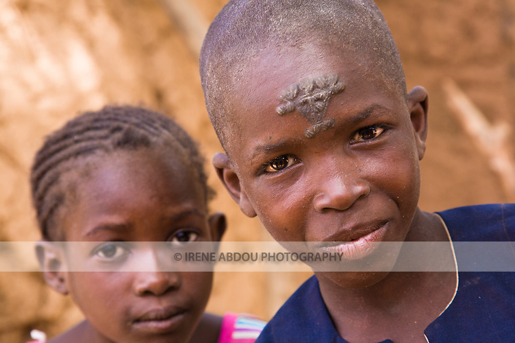A young boy in Torodi, Niger sports the traditional facial scarring of the Fulani tribe.  The scarring is done with a razor blade, and charcoal powder mixed with cream is rubbed into the fresh wound to create the darkened effect.