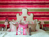 A glamorous, feminine bedroom in shades of red and pink. A bed has a white cover with a fur edging and a shaped, upholstered headboard. A collection of cushions with vibrant floral patterns sit on the bed. Lamps with pink shades stand on bedside cabinets either side of the bed.