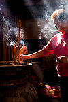 A woman prays in front of incense urn in Yanshui's Martial Temple. Yen Shui Village, Tainan County, Taiwan