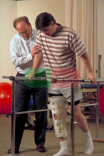physical therapist helping patient with injured leg to walk