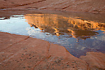 Paria Canyon-Vermillion Cliffs Wilderness, AZ / DEC:  In North Coyote Buttes, sandstone buttes illuminated by the morning sun reflects into an icy water pocket.