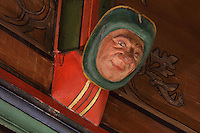 Carved and painted roof bracket with man smiling, architectural detail of the painted wooden ceiling in the shape of a boat's hull, in the Salle des Povres or Room of the Poor, almost 50m long, in Les Hospices de Beaune, or Hotel-Dieu de Beaune, a charitable almshouse and hospital for the poor, built 1443-57 by Flemish architect Jacques Wiscrer, and founded by Nicolas Rolin, chancellor of Burgundy, and his wife Guigone de Salins, in Beaune, Cote d'Or, Burgundy, France. The hospital was run by the nuns of the order of Les Soeurs Hospitalieres de Beaune, and remained a hospital until the 1970s. The building now houses the Musee de l'Histoire de la Medecine, or Museum of the History of Medicine, and is listed as a historic monument. Picture by Manuel Cohen