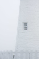 A white-on-white shot of the lighthouse in the fog.