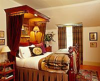 A pair of plaid ochre curtains match the duvet on an antique half-tester bed in this bedroom