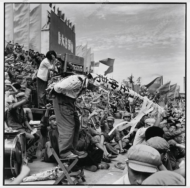 """At a rally in Red Guard Square, provincial Party secretary and first Party secretary of Harbin Ren Zhongyi, after having his face smeared with black ink, is forced to wear a dunce cap and a placard around his neck with the accusatory label """"black gang element"""" while standing on an unstable chair with his hands behind his back holding a string attached to the ill-fitting hat. Harbin, 26 August 1966"""
