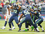 Seattle Seahawks defensive unit celebrates a quarterback sack by defensive end Michael Bennett (72) in their game at CenturyLink Field in Seattle, Washington on December 29, 2013.  The Seahawks held the Rams to18 yards rushing and 157 passing yards. The Seahawks clinched the NFC West title and home-field advantage throughout the playoffs with a 27-9 victory over the St. Louis Rams.  ©2013. Jim Bryant Photo. ALL RIGHTS RESERVED.