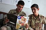Two Iraqi soldiers catch up on men's fashion at their firm base in Hit, Iraq on Friday September 23, 2005.