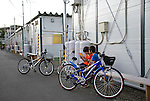 Young children play games while sitting on a bench in a temporary housing estate established for those who lost their homes during the March 11 quake and tsunami in Natori City, Miyagi Prefecture Prefecture, Japan on 08 Sept. 2011. Photograph: Robert Gilhooly