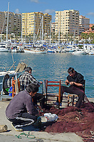 Fishermen repair fishing nets, quay, Mediterranean, Mediterraneo, Estepona, Malaga, Andalucia, Andalusia, Spain, Espana, Costa del Sol, tourism, travel, holidays, 201302201119..Copyright Image from Victor Patterson, 54 Dorchester Park, Belfast, UK, BT9 6RJ..Tel: +44 28 9066 1296.Mob: +44 7802 353836.Voicemail +44 20 8816 7153.Skype: victorpattersonbelfast.Email: victorpatterson@me.com.Email: victorpatterson@ireland.com (back-up)..IMPORTANT: If you wish to use this image or any other of my images please go to www.victorpatterson.com and click on the Terms & Conditions. Then contact me by email or phone with the reference number(s) of the image(s) concerned.