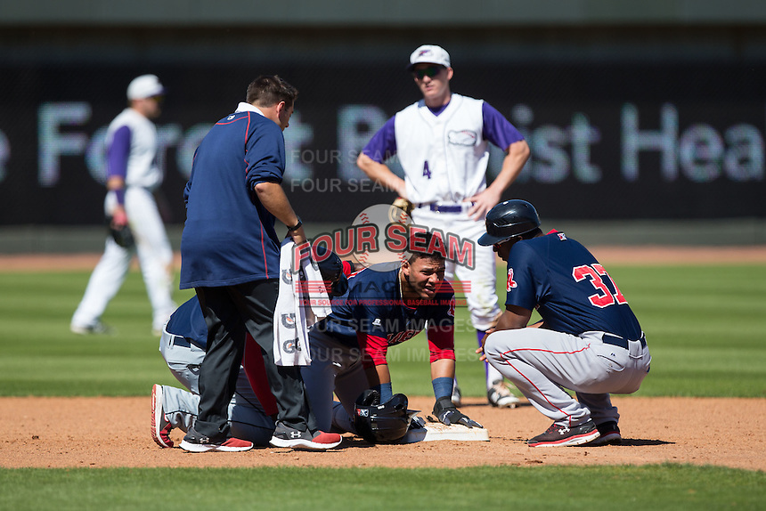 Yoan Moncada (center) is checked out by the trainer and teammate Carlos Mesa (37) after being hit in the face with a throw as he stole second base during the game against the Winston-Salem Dash at BB&T Ballpark on April 17, 2016 in Winston-Salem, North Carolina.  The Red Sox defeated the Dash 3-1.  (Brian Westerholt/Four Seam Images)