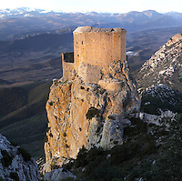 "Queribus Castle or Chateau de Queribus, Cathar Castle, Cucugnan, Corbieres, Aude, France. This view shows the steep rocky cliffs of its hilltop location and Pyrenees in the distance. The castle, built from 13th to 16th centuries, is considered the last Cathar stronghold. It sits on a high peak at 728m. It is one of the ""Five Sons of Carcassonne"" or ""Cinq Fils de Carcassonne"". It is a listed monument historique and has been fully restored, restoration work being completed in 2002. Picture by Manuel Cohen"