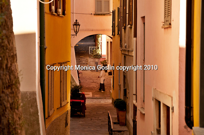 Looking down a path between houses in Varenna, Italy with a chef standing outside a restaurant, taking a break in the background.