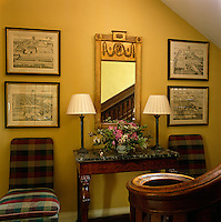 A series of four framed architectural drawings flanks a gilt-framed mirror in the narrow hall at the foot of the stairs