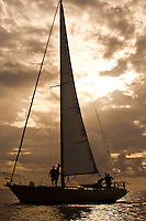 Yacht at sunset returning to harbor under mainsail