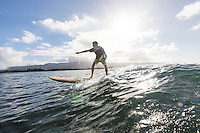 A man learns to surf at Pua'ena Point, North Shore, O'ahu.