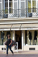 Stylish French woman passes Max Mara boutique shop in the fashionable area of Pau in the Pyrenees, France