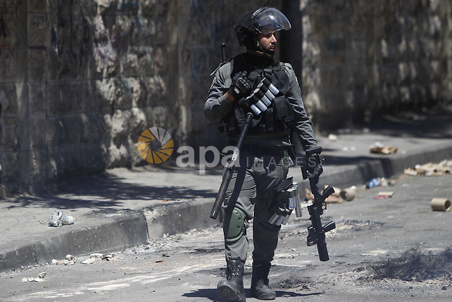 An Israeli policeman stands guard during clashes with Palestinian stone-throwers on April 25, 2015 in Al-Tur neighbourhood of annexed Arab east Jerusalem, after Israeli police shot dead a knife-wielding Palestinian who attempted to stab colleagues at an east Jerusalem checkpoint. The 17-year-old assailant from Al-Tur managed to get past one checkpoint but was brought down at a second near Al-Zaim without any police casualties, a spokeswoman said. Photo by Saeb Awad
