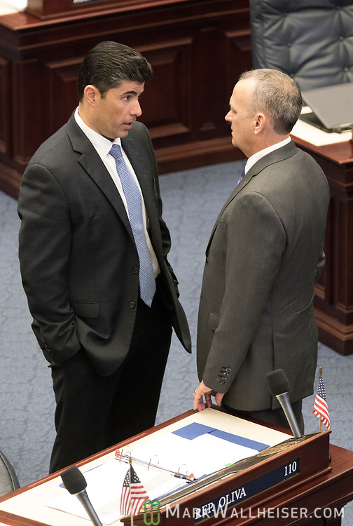 Rep. Jose Oliva, left, (R-Hialeah) talks with Speaker of the House Richard Corcoran (R-Lutz) on the House floor as the Florida House of Representatives convenes at the Florida Capitol.