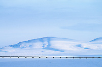 The Trans Alaska oil pipeline stretches across the snow covered tundra, Slope mountain, Arctic, Alaska.