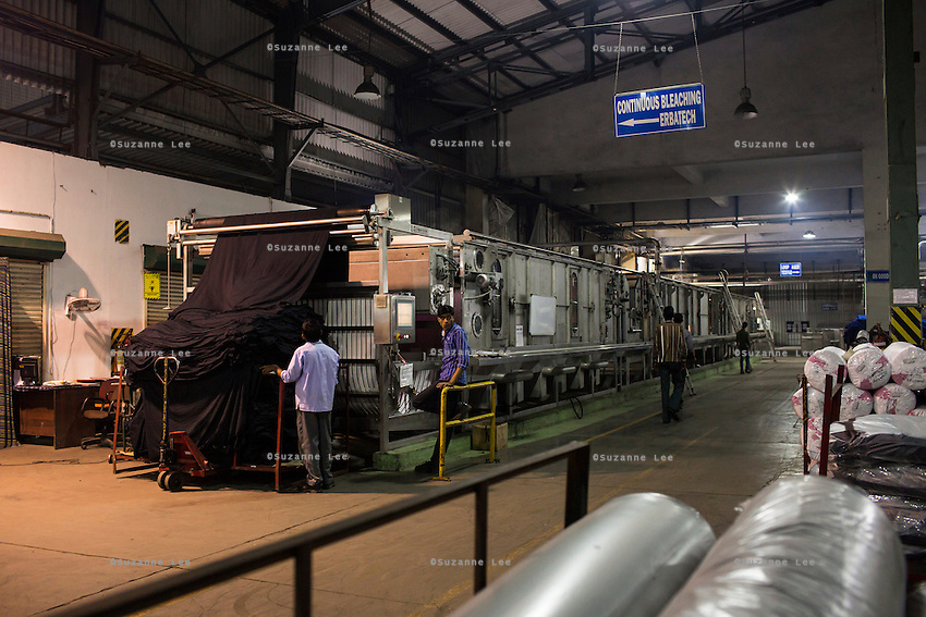 Coloured textiles being tested through the Continuous Bleaching Machine in the Pratibha vertically integrated garment unit in Indore, Madhya Pradesh, India on 11 November 2014. Photo by Suzanne Lee for Fairtrade