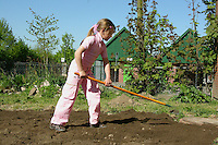 Schulgarten, Fläche am Schulgebäude, auf der ein Schmetterlingsgarten angelegt werden soll, Garten der Grundschule Nusse wird als Projektarbeit von einer 1. Klasse gestaltet, Mädchen verteilt frischen Mutterboden zur Bodenverbesserung; Gartenarbeit