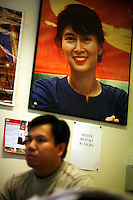 "Behind journalist Htet Aung Kyan is a portrait of Aung San Suu Kyi, above note saying ""NEVER REPORT RUMORS"".  Democratic Voice of Burma is radio and TV station run by exiled Burmese. Opposing the government, the DVB has been transmitting, from the Norwegian capitol Oslo, into Burma since 1992."