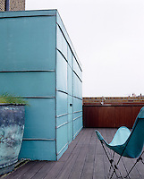 A copper roof extension on the roof terrace which has a wooden decking and outdoor kitchen