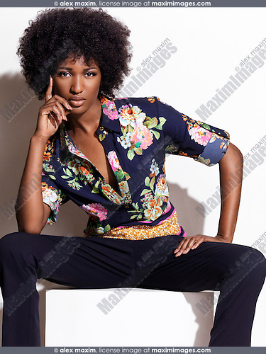 Beautiful african american black woman with big natural hair wearing dark blue floral shirt and pants. Fashion photo isolated on white background.