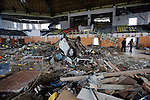 A car and some sports gear, such as a baseball jersey and a soccer ball, lie among the debris inside the city sports center in Rikuzentakata City, Iwate Prefecture, Japan on 11 Mar. 2012.  Hundreds of people paid their respects at the center, inside which 100 people were drowned,  following  a remembrance service held nearby to mark the one year anniversary of last year's magnitude 9 earthquake and tsunamis in Japan's northeast..Photographer: Robert Gilhooly