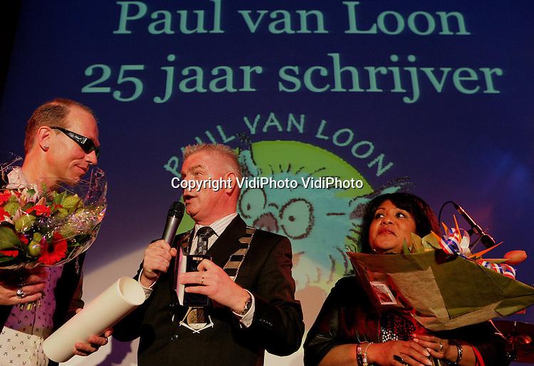 Foto: VidiPhoto..ARNHEM - Kinderboekenschrijver Paul van Loon is zaterdag benoemd tot Officier in de Orde van Oranje-Nassau tijdens de Dolfje Weerwolfjedag in Burgers' Zoo in Arnhem. De loco-burgemeester van Heusden, de woonplaats van Van Loon, spelde hem de hoge onderscheiding op. Paul van Loon is dit jaar 25 jaar schrijver. In die periode schreef hij meer dan 90 boeken en werd hij acht keer winnaar van de Nederlandse Kinderjury. V.l.n.r. Paul van Loon, loco-burgemeester Ben Groen en vrouw Hadidja.